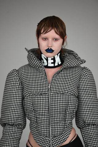 LULA LAORA AW21 Getty Images, womenswear model has blue lips and short hair. She wears a houndstooth puffer jacket and a black top with a neck piece that says SEX.