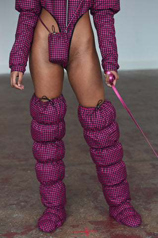 LULA LAORA AW21 Getty Images, womenswear model wears pink fine houndstooth puffy shoes that are thigh high. She also wears a small pink houndstooth bag and a puffer jacket bodysuit with a high leg in pink. She also holds a pink leash.