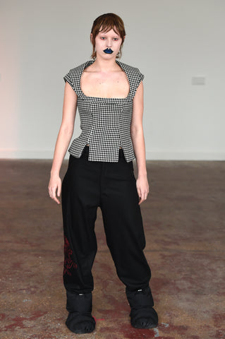 LULA LAORA AW21 Getty Images, womenswear model wears sleeveless houndstooth top with two small front slits and a U shape neckline. She also wears black oversized trousers and puffy shoes.