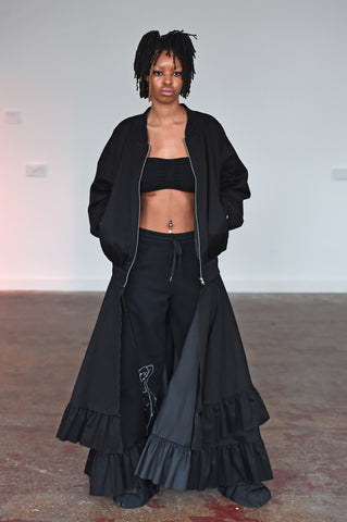 LULA LAORA AW21 Getty Images, womenswear model wears black bralette top, joggers/sweatpants with a white lady print, and a black bomber jacket with two layers.