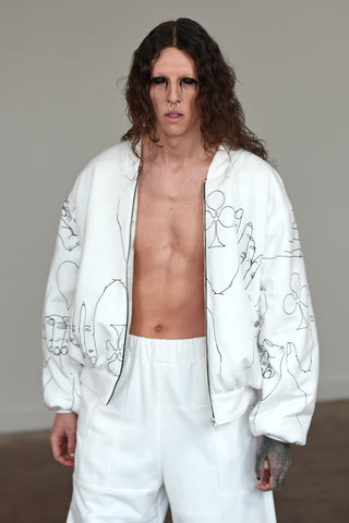 LULA LAORA AW21 Getty Images, menswear model wears a white bomber jacket with black illustrations and white large joggers/sweatpants.