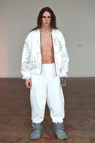 LULA LAORA AW21 Getty Images, menswear model wears a white bomber jacket with black illustrations and white large joggers/sweatpants. and houndstooth puffy shoes.