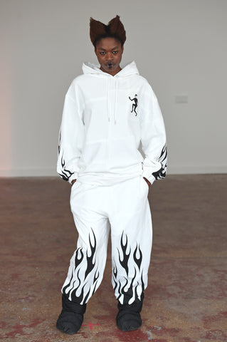 LULA LAORA AW21 Getty Images,womenswear model wears white tracksuit and black puffy shoes. The hoodie has a black evil lady logo and flames on the sleeves and hem of the trousers.