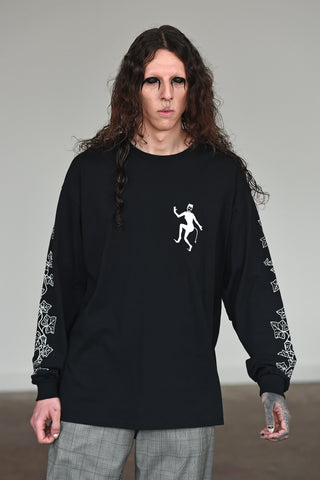 LULA LAORA AW21 Getty Images, menswear model wears check trousers. Also wears a black long sleeved t-shirt with ivy illustrations on the sleeves and a white evil lady logo.