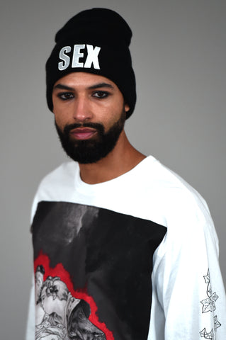 LULA LAORA AW21 Getty Images, black beanie with sex written on it. Model wears long sleeved white t-shirt with graphic print in black, white and red.