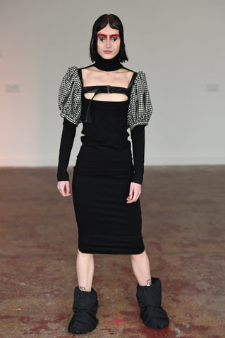 LULA LAORA AW21 Getty Images, womenswear model wears black puffy shoes with fitted back midi dress with a high neck and a cut-out neckline. Also wears a houndstooth harness.