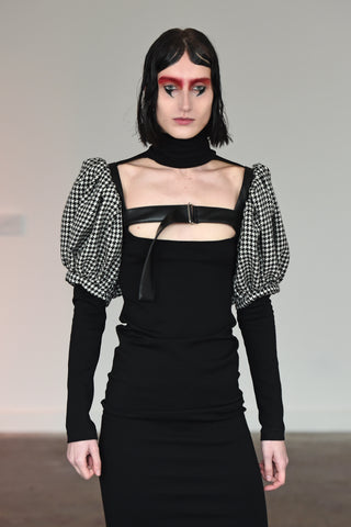 LULA LAORA AW21 Getty Images, womenswear model wears fitted back midi dress with a high neck and a cut-out neckline. Also wears a houndstooth harness.