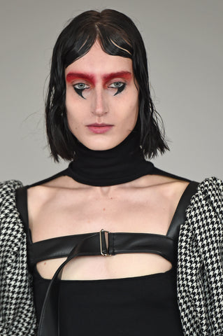 LULA LAORA AW21 Getty Images, womenswear model wears a black high neck and a cut-out neckline. Also wears a houndstooth harness.