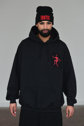 LULA LAORA AW21 Getty Images, menswear model wears a black beanie with the words erotic in red. the hoodie is black with a Red Devil lady logo, he also wears black sweatpants or joggers.