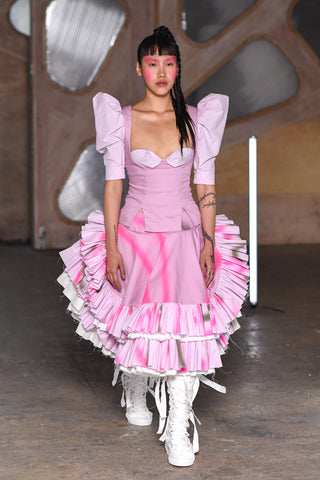 Lula Laora runway Getty pink eyebrows, pink victorian top with puffy sleeves, ruffled midi skirt and white high top laced sneakers