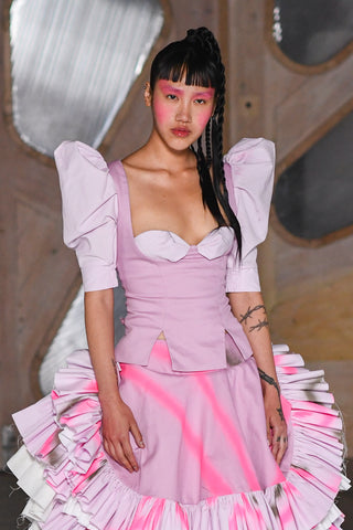 Lula Laora runway Getty pink eyebrows, victorian style top wit puffy sleeves, ruffled neon and pink skirt mid-length