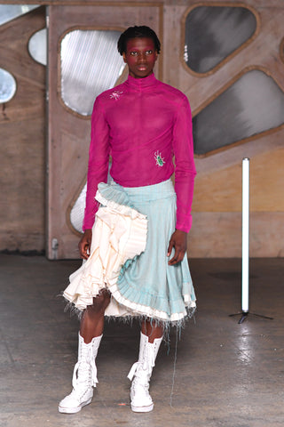 Lula Laora runway Getty pink eyebrows, menswear, mesh long sleeved fuchsia top with a high neck and embroidered beetles on it. white high top sneakers with lace up closing. Aqua light blue skirt with white ruffles.