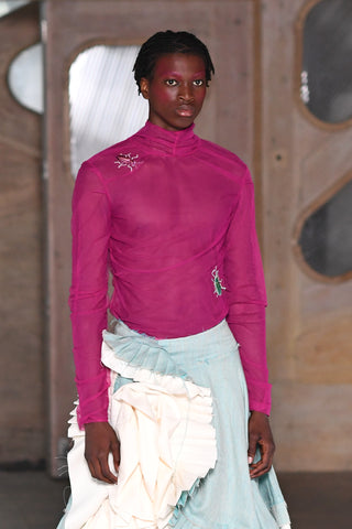 Lula Laora runway Getty pink eyebrows, mesh long sleeved fuchsia top with a high neck and embroidered beetles. aqua, light blue and white ruffled skirt.