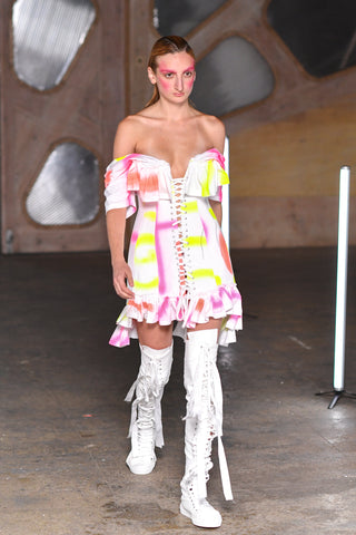Lula Laora runway Getty pink eyebrows, white mini dress with neon pink and yellow patterns, semi-sweetheart neckline, off the shoulder dress, high top long laced up shoes