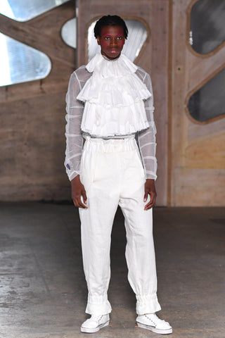 Lula Laora runway Getty pink eyebrows, white mesh long sleeved top with ruffled bib, white sneakers and white high-waisted trousers.