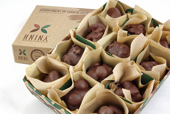HNINA Organic Fair Trade Raw Dark Chocolate 12 delicious nourishing rocks with sprouted nuts and sprouted seeds truffles collection enclosed individually into a compostable luxurious HNINA kraft paper and inserted into a luxurious and compostable kraft paper box