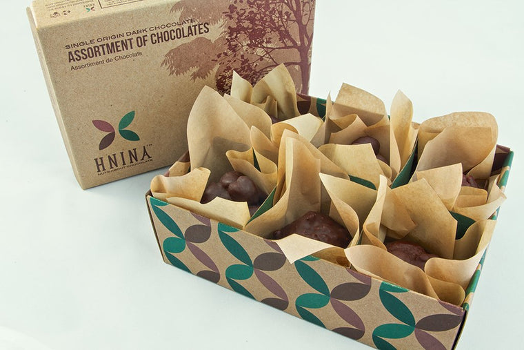 HNINA Organic Fair Trade Raw Dark Chocolate 6 delicious nourishing boulders with sprouted nuts and sprouted seeds truffles collection enclosed individually into a compostable luxurious HNINA kraft paper and inserted into a luxurious and compostable kraft paper box
