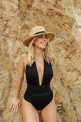 Black one-piece swimsuit Eva shown on model at the beach.