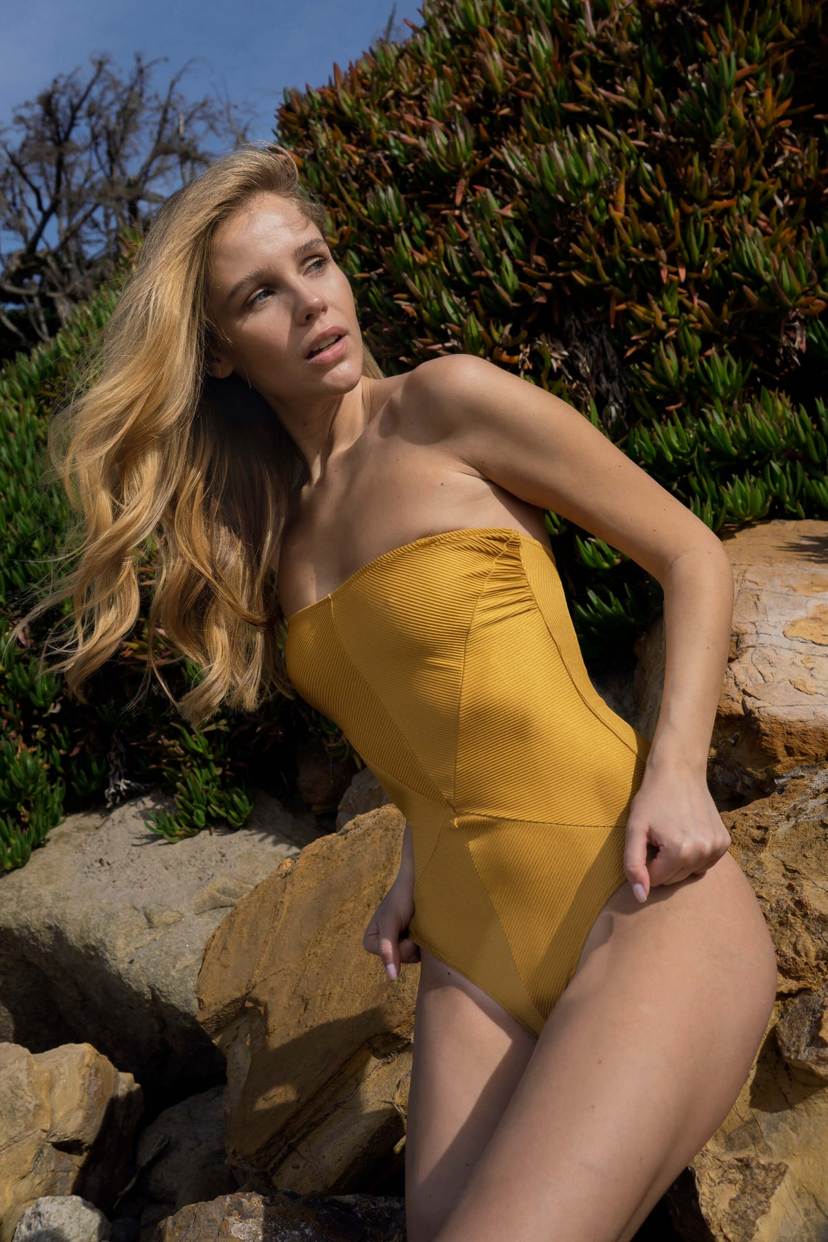 Model wears the Hannah Swimsuit in Ribbed Gold on the beach in Malibu, CA.
