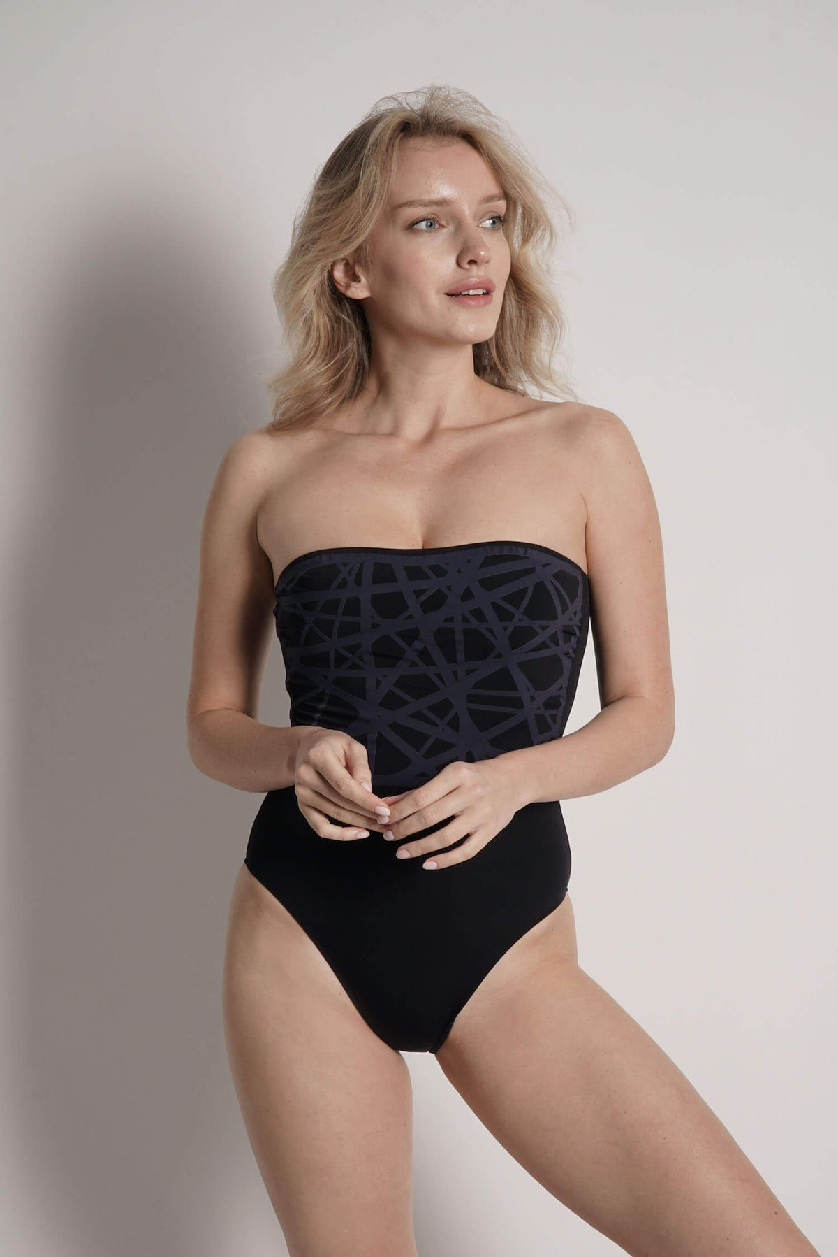 Model wears Angela one piece swimsuit in black with navy laser details.