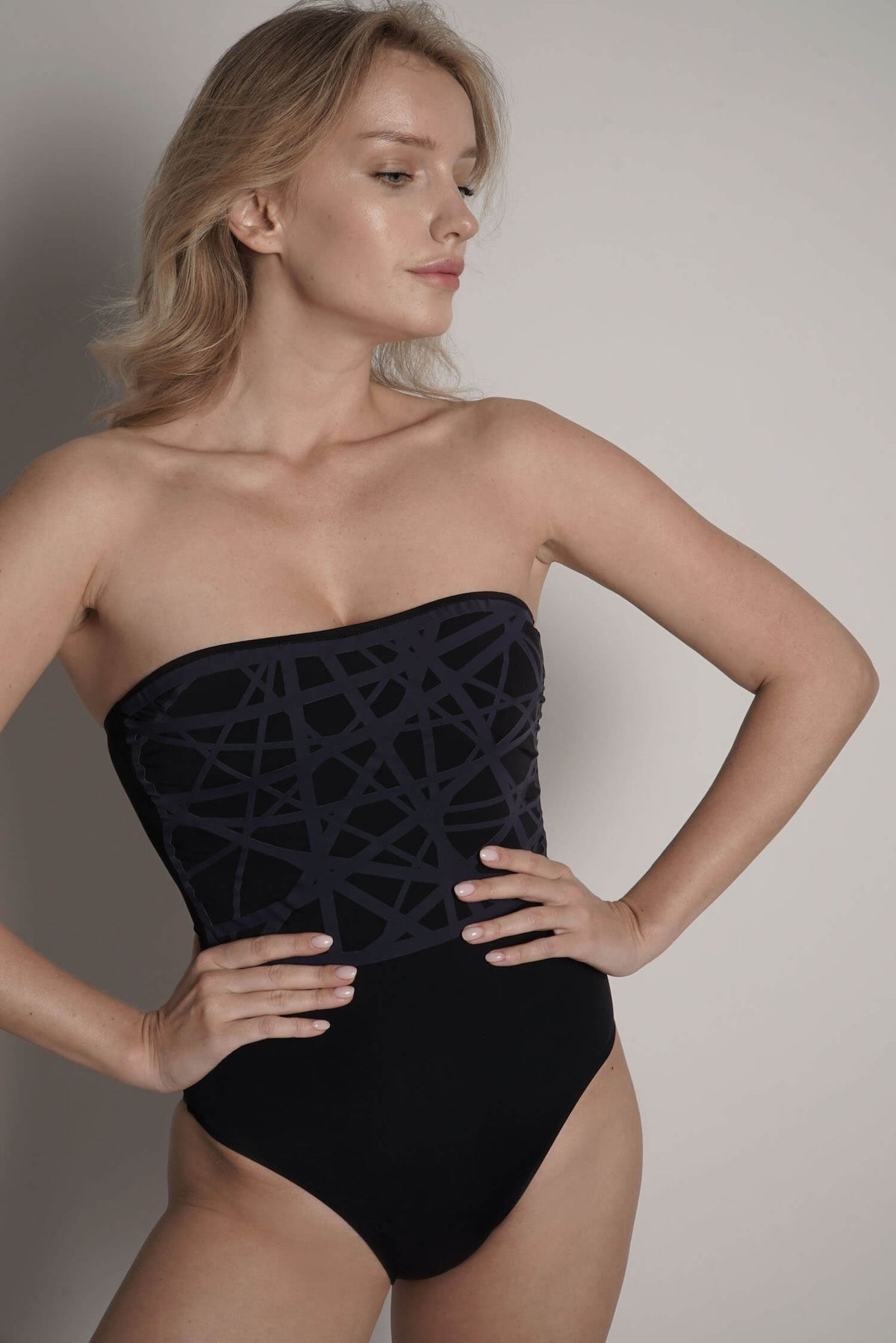 Model shows Angela one piece swimsuit in black with navy laser details.