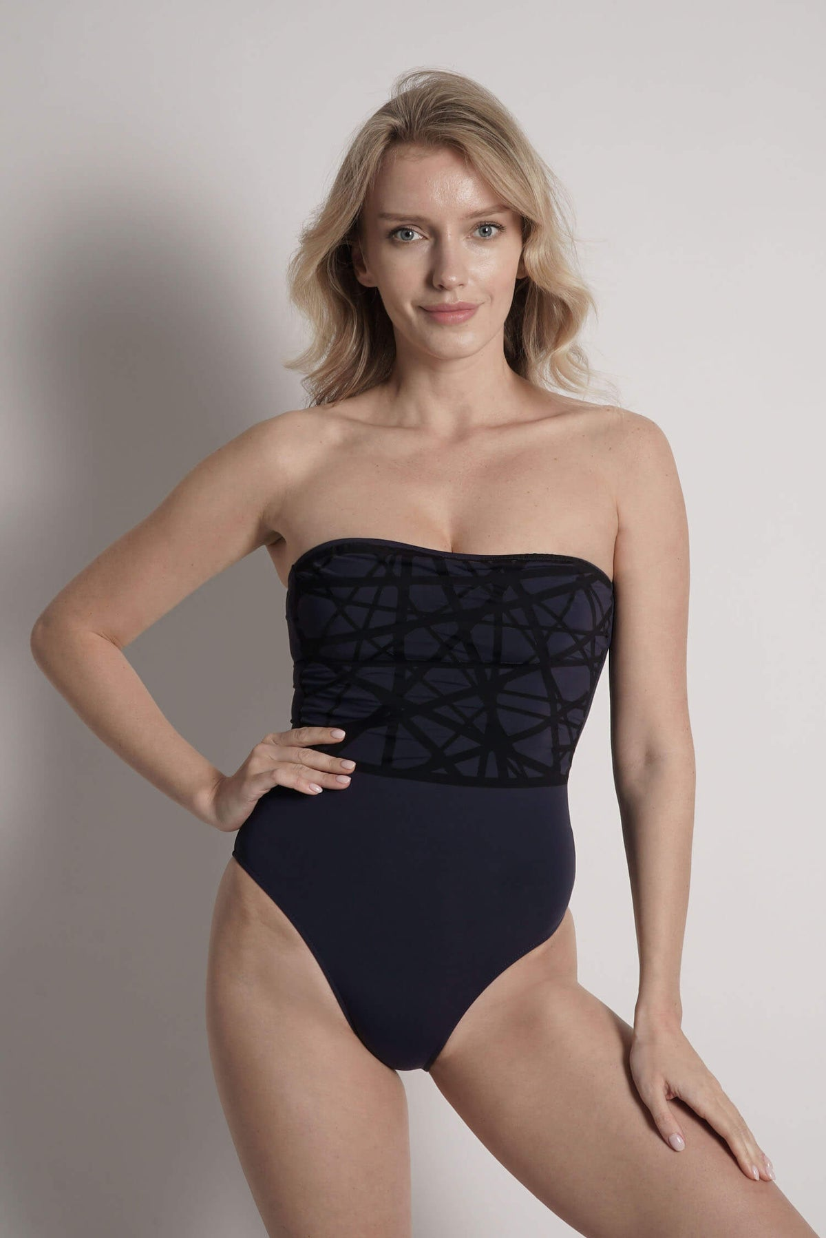 Model wears Angela one piece swimsuit in navy with black laser details.