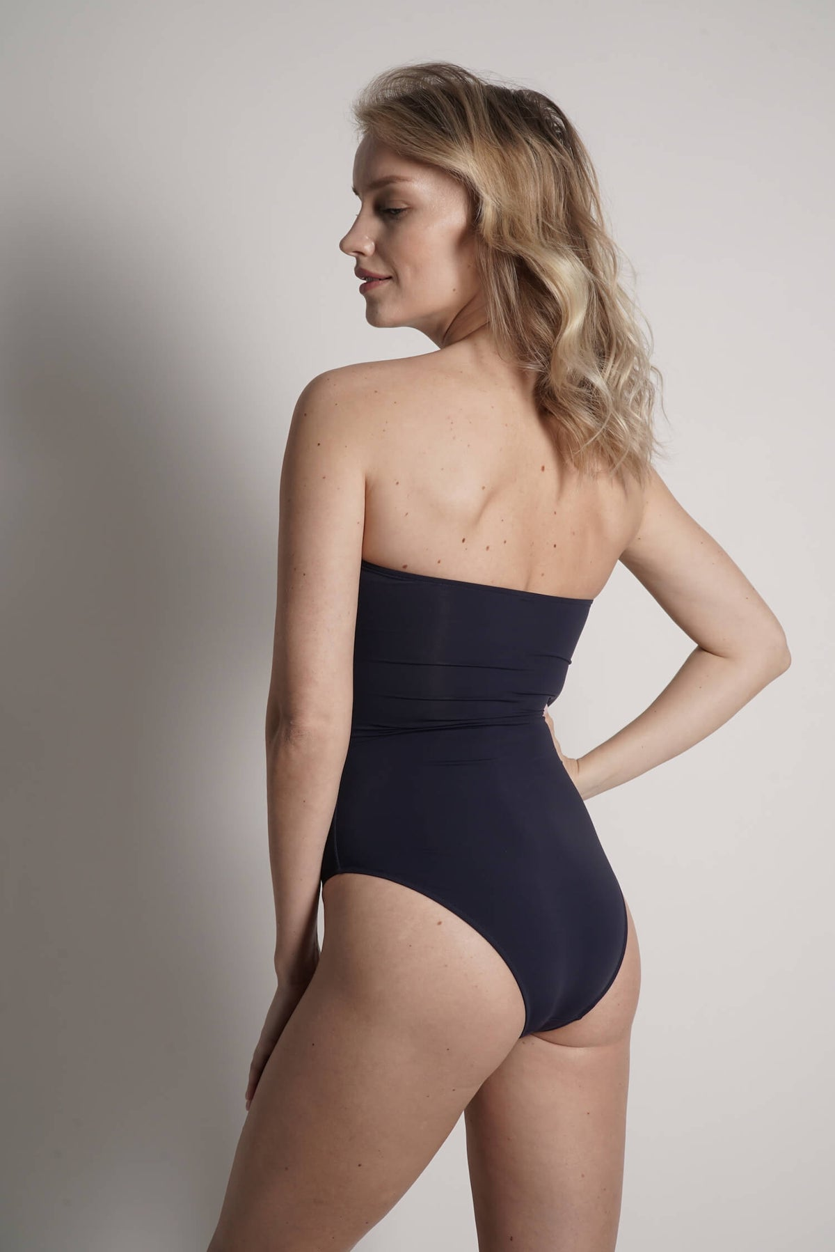 Back of Angela one piece swimsuit in navy with black laser details.