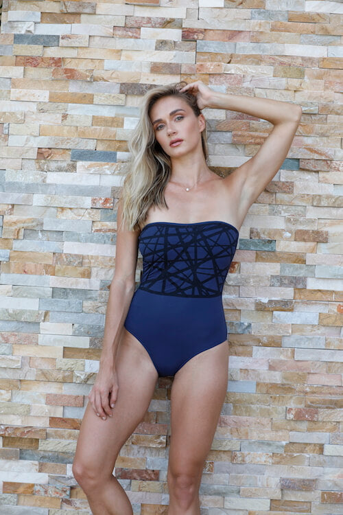 Model shows Angela one piece swimsuit in navy with black laser details.
