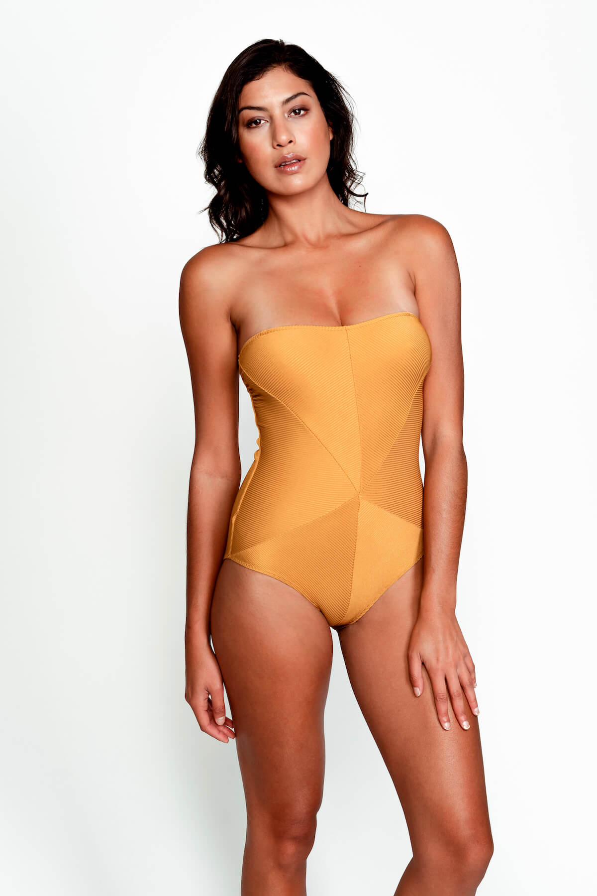 Model wears the Hannah Swimsuit in Ribbed Gold. Front image, without straps.