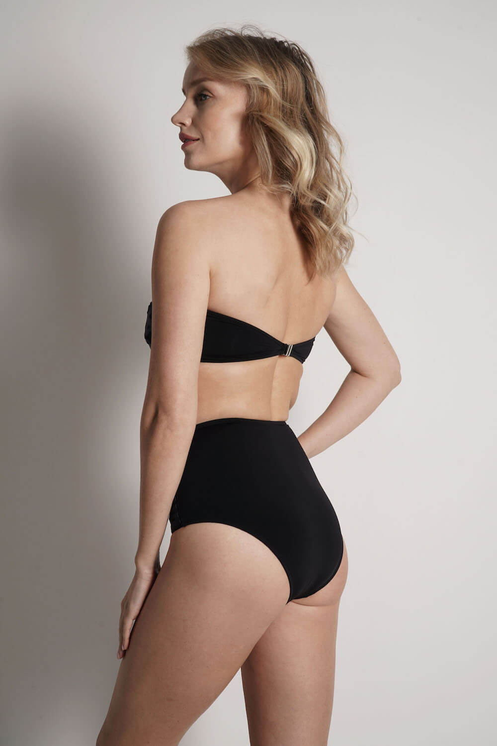 Back of Lillian bandeau bikini top in black with navy laser details