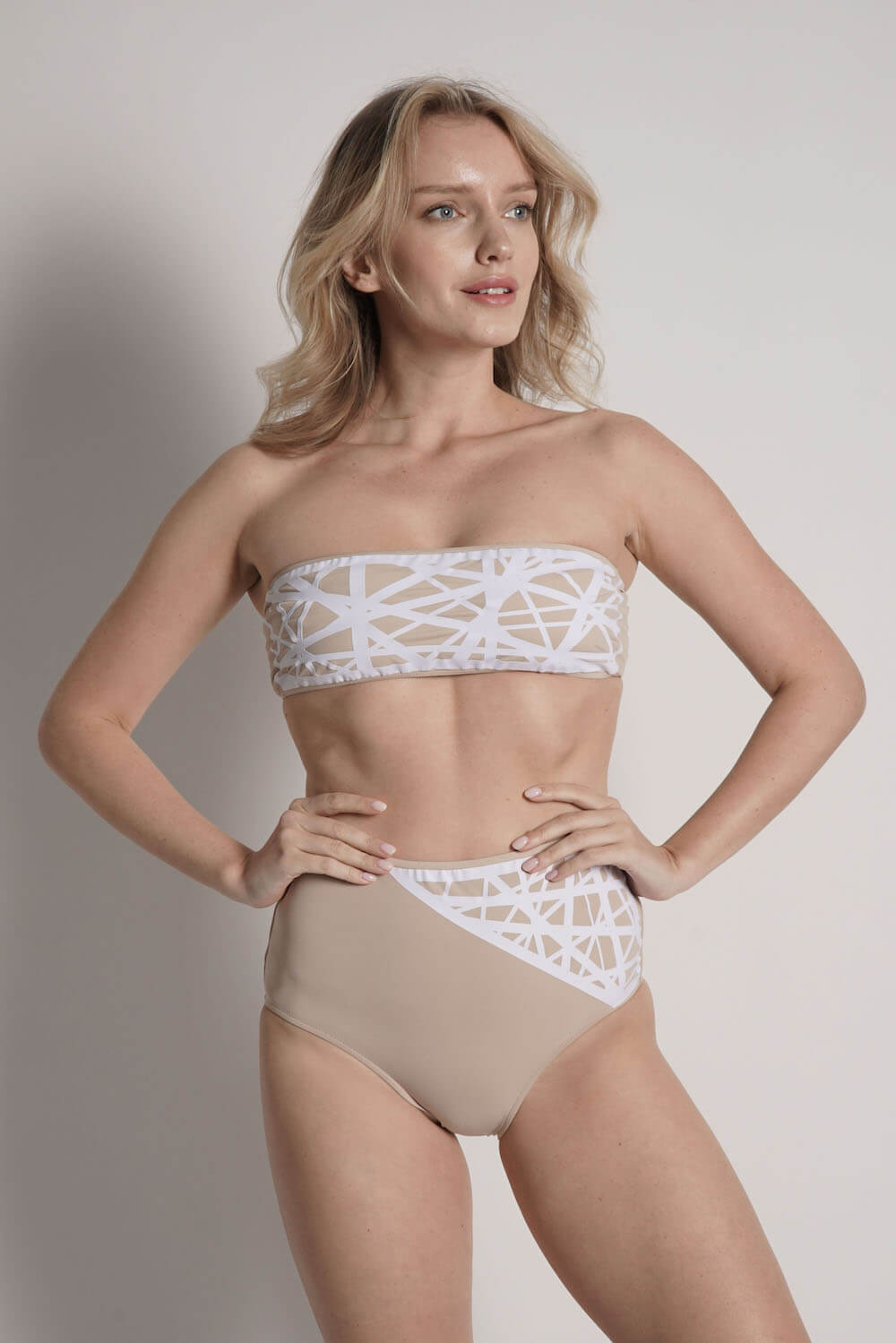 Model wears Lillian high waisted bikini bottom in camel with white laser details