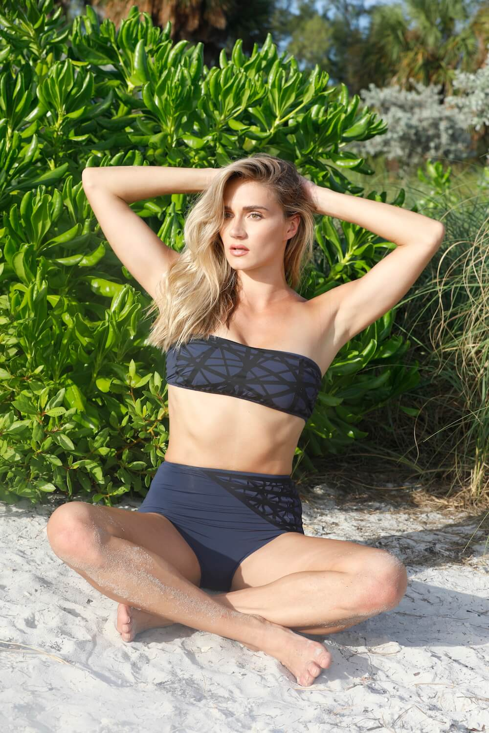 Model wears Lillian bandeau bikini top in navy with black laser details