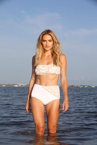 Model on the beach wears Lillian high waisted bikini bottom in white with camel laser details