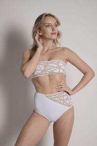 Model wears Lillian high waisted bikini bottom in white with camel laser details