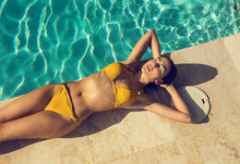 Nina halter bikini top in mustard by the pool
