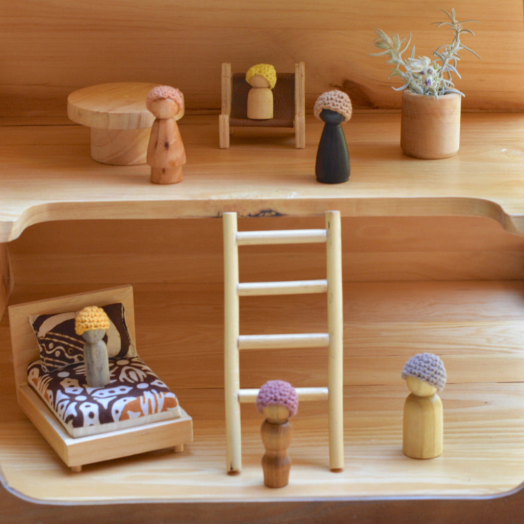 wooden peg dolls in a doll house