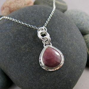 Gemstone love knot necklace by Mikel Grant Jewellery. Artisan made natural pink sapphire teardrop in textured sterling silver.