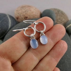Artisan made soft blue chalcedony joy drop earrings in sterling silver by Mikel Grant Jewellery. Displayed on a hand.