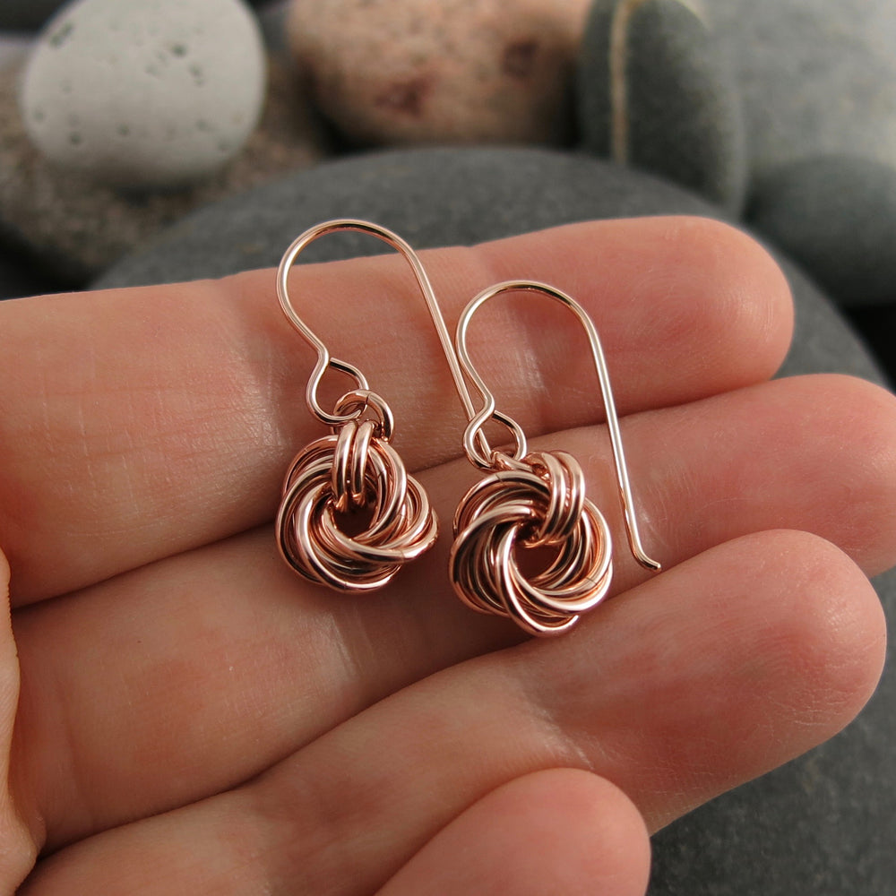 Algerian love knot earrings in 14K rose gold fill by Mikel Grant Jewellery. Artisan made.  Displayed on a hand.