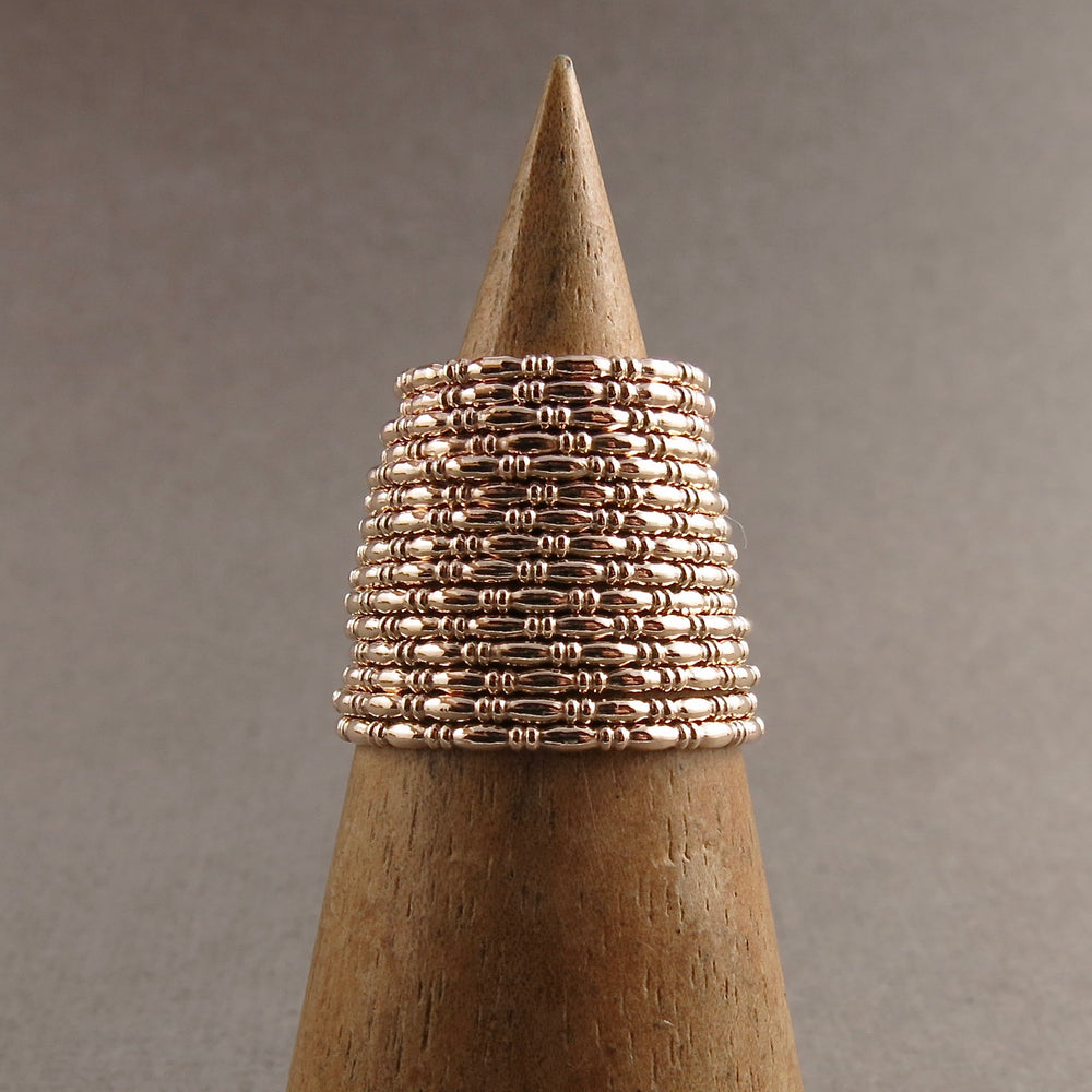 Artisan made gold uniquely patterned stacking ring by Mikel Grant Jewellery.  Displayed in a group.