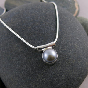 Pearl solitaire necklace by Mikel Grant Jewellery. Silvery-grey button pearl in sterling silver.