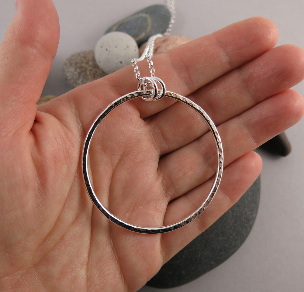 "Artisan made open circle necklace in thick, hammer textured sterling silver with a long 30"" silver rolo chain by Mikel Grant Jewellery.  Seen here displayed on a hand."