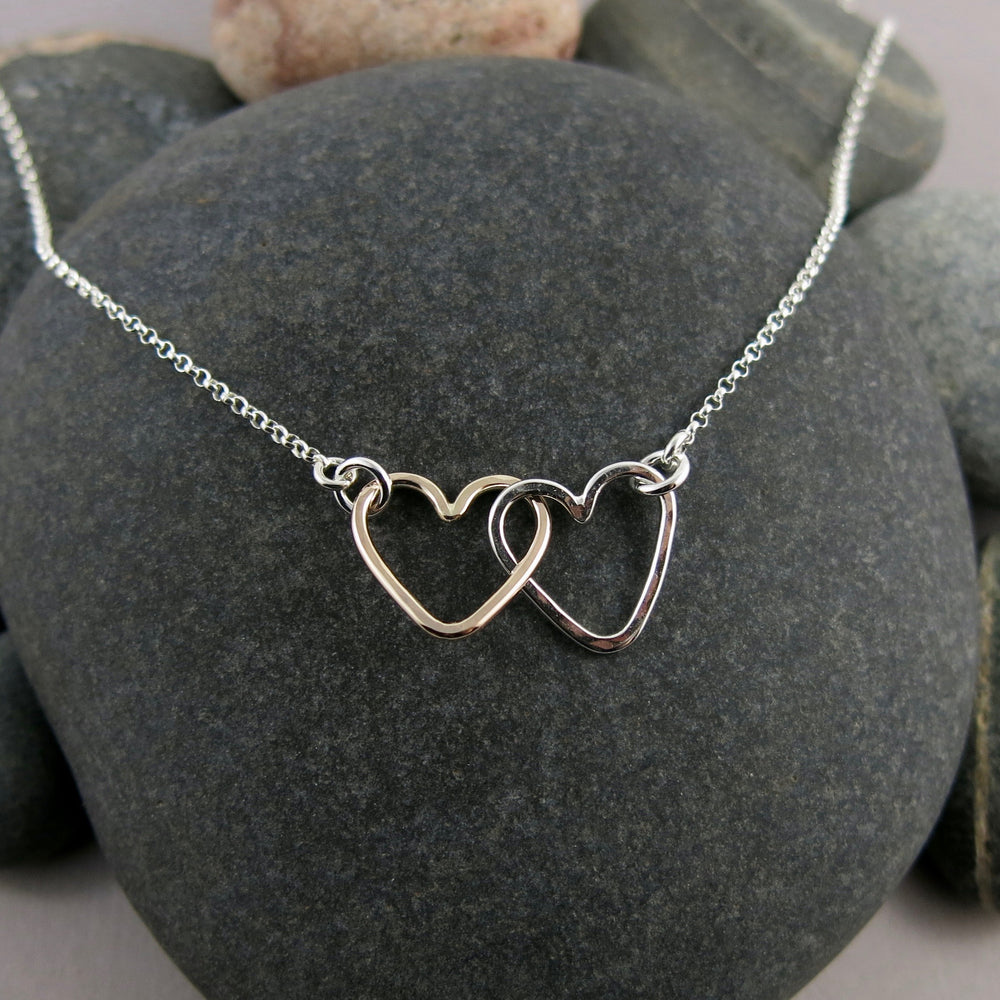 Hearts Embrace Necklace in Gold and Silver by Mikel Grant Jewellery.  Artisan made interlocking hearts necklace.