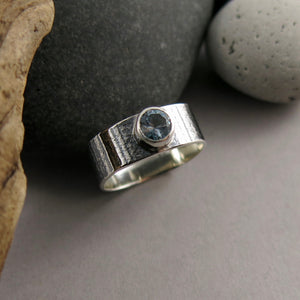 Artisan made jewel drop gemstone ring by Mikel Grant Jewellery. Round faceted ice blue topaz on a soft square sterling silver band with oxidized raw silk texture design.
