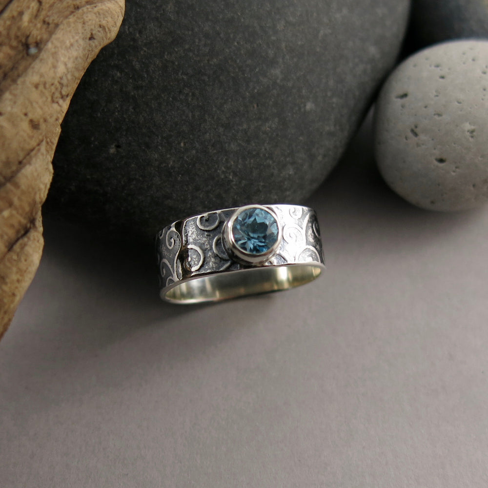 Jewel drop gemstone ring by Mikel Grant Jewellery. Faceted round Swiss blue topaz gemstone on a soft square sterling silver ring band with an oxidized tendrils design.