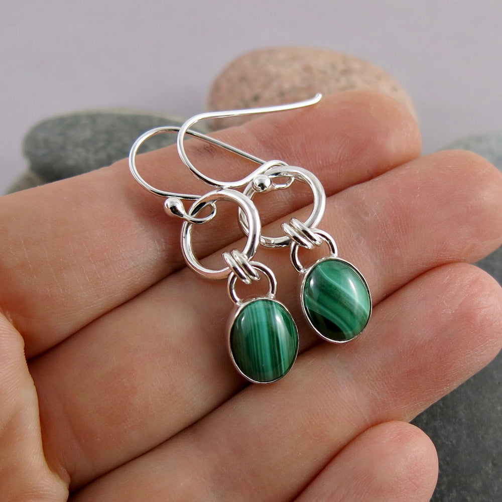 Artisan made malachite and silver joy drop earrings by Mikel Grant Jewellery. Displayed on a hand.