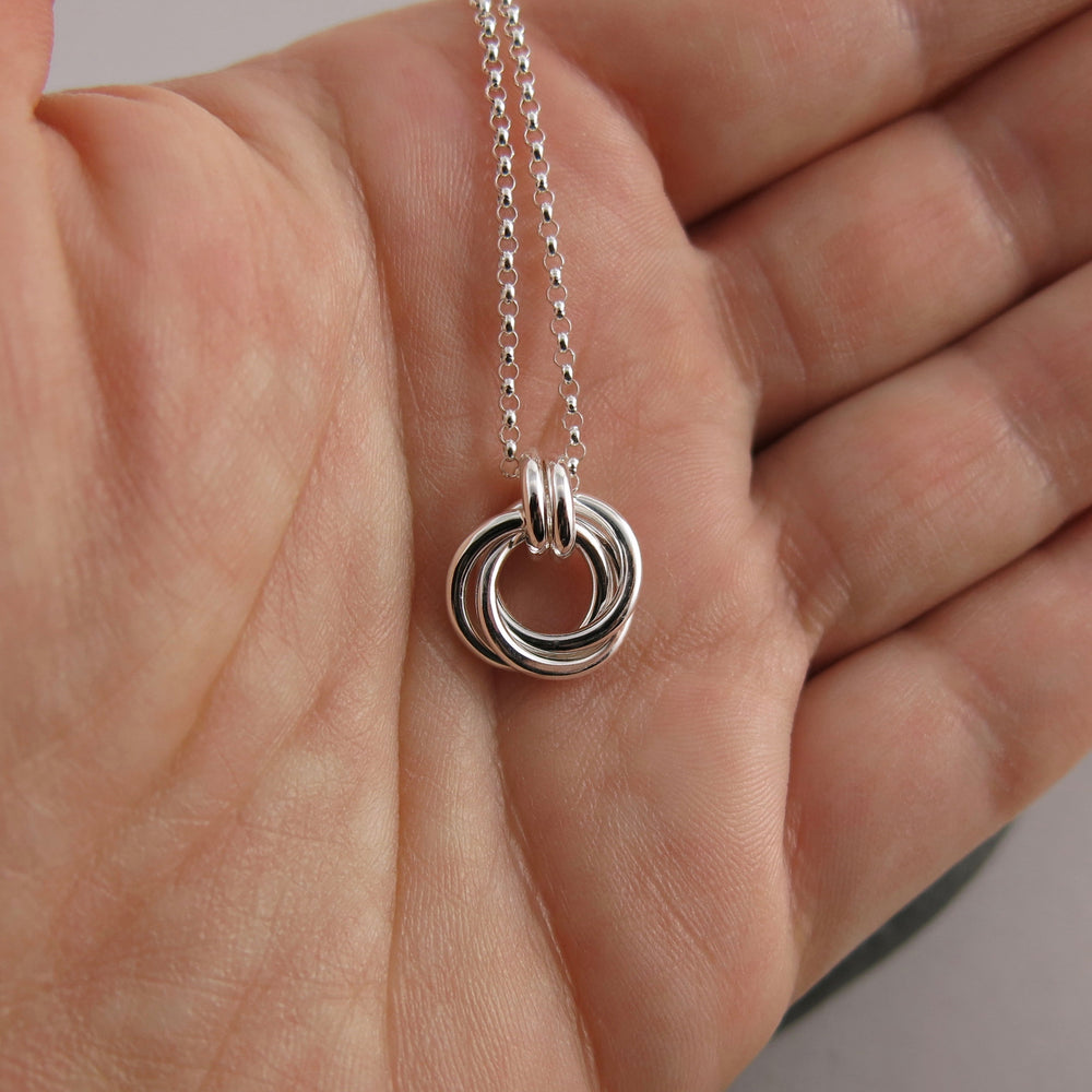 Mini timeless love knot necklace in sterling silver displayed on a hand by Mikel Grant Jewellery. Artisan made infinite knot jewellery.