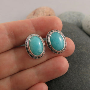 Artisan made sterling silver and natural amazonite oval stud earrings by Mikel Grant Jewellery. Featuring a pair of turquoise-blue semi-precious gemstones.  Displayed on a hand.