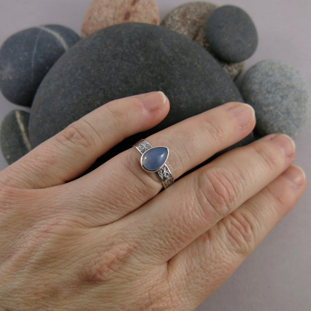 Artisan made chalcedony teardrop on an oxidized textured sterling silver soft square ring by Mikel Grant Jewellery.  Displayed on a hand.