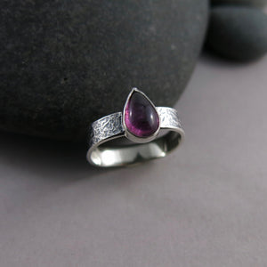 Artisan made one of a kind pink tourmaline teardrop ring on an oxidized textured sterling silver soft square band by Mikel Grant Jewellery.